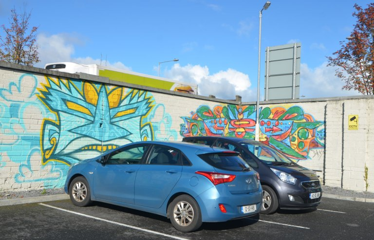 two cars parked in the corner of a car park, blocking views of two small murals, one on each wall of the corner. One is a stylized young man's face in blue and yellow.