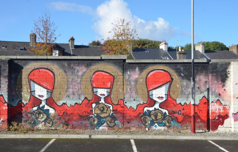 mural on a brick wall in a car park, with houses behind, three stylized women with bright red hair, flowing to their shoulders, all holding bouquets of flowers