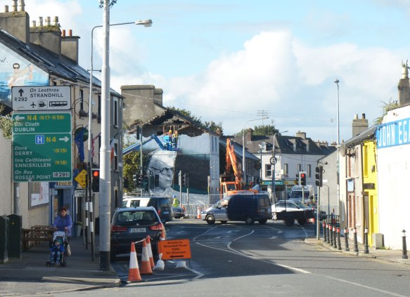 city streets in Sligo Ireland with houses, pedestrians and road. A crane is being used to demolish the top part of a house. On the side of that house, exterior, is a large mural that is a portrait of the poet William Butler Yeats (W.B. Yeats)