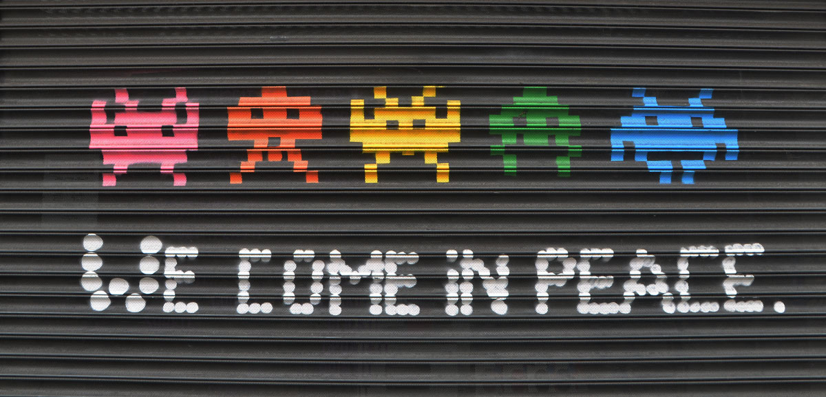a line of 5 space invader creatures from the video game, with the words we come in peace under them.