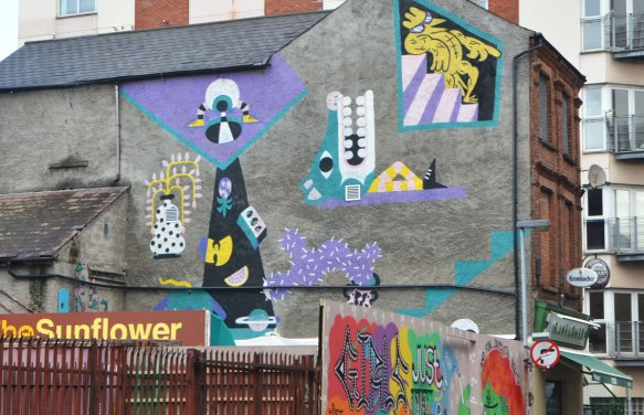 a collection of street art pieces on the side of a greybuilding, painted in purple, yellow and turquoise mostly. Abstract shapes