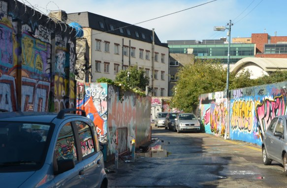 construction hoardings covered with street art and graffiti with cars parked beside them.