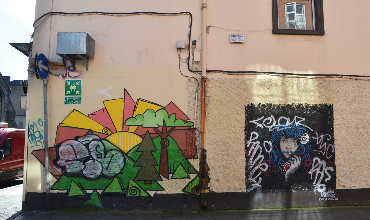 two street art paintings on a yellowish stucco wall, side of a building. One is a stylized landscape with trees, mountains and sun that has a large tag on top of it. The other is a person with long blue hair, hand by chin, head and shoulders only, by Evolve Urban Art
