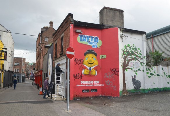 an ad for Tayto emoji app, red mural with yellow faced man cartoonish character