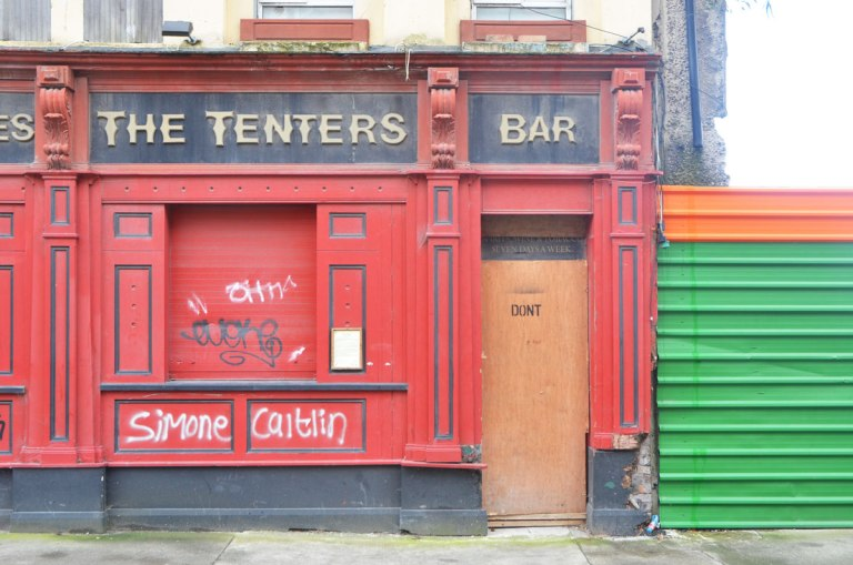 exterior of the The Tenters Bar in red with black trim, closed and boarded up. The door is brown. Stencilled on the door is the word Don't. Simone and Caitlin are also written in white on the red wall.