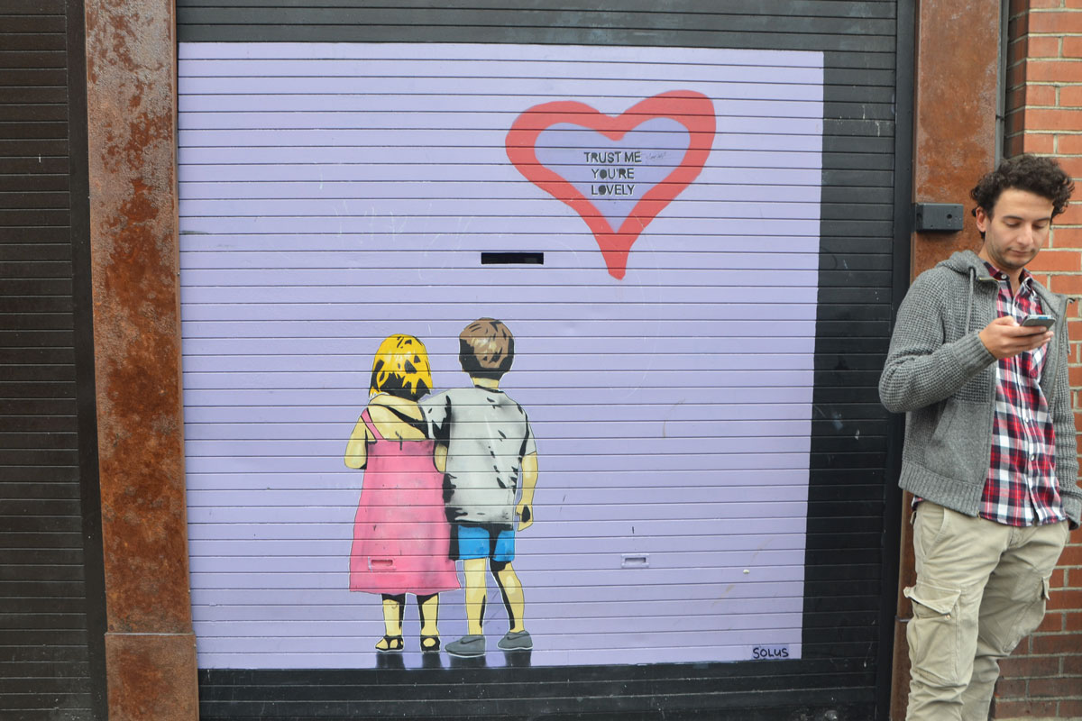 a young man on his phone is standing in front of a street art painting, lavender colour background with a boy and girl withtheir back to the viewer. THe boy has his arm around the shoulder of the girl. There is a heart in the upper right corner, outlined in red and containing the words Trust me you're lovely.