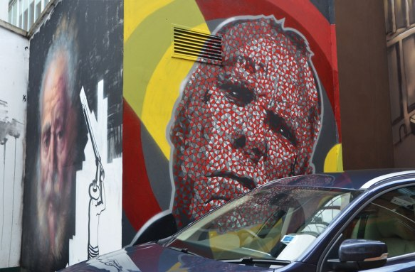 two murals on two sides of a corner. One is a realistic painting of an old man and the other is also a man's head but it is done in red, white and black shapes.