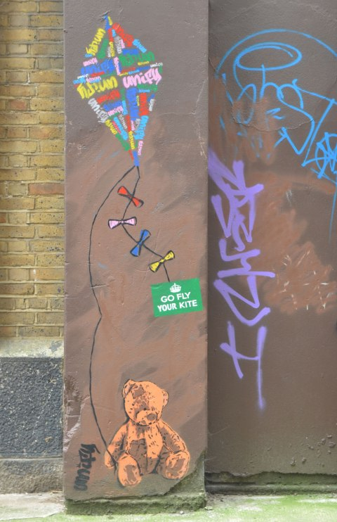 a teddy bear paste up or stencil sits on the sidewalk. he is holding a kite string in his paw and the kite is above him on the wall. A green sticker says go fly your kite. The signature says unify. the word unify is written many times in the kite in different colours to make a design on the kite.