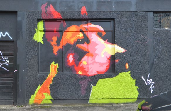 mural on black wall of a dog's head and neck in oranges, red, and pinks,