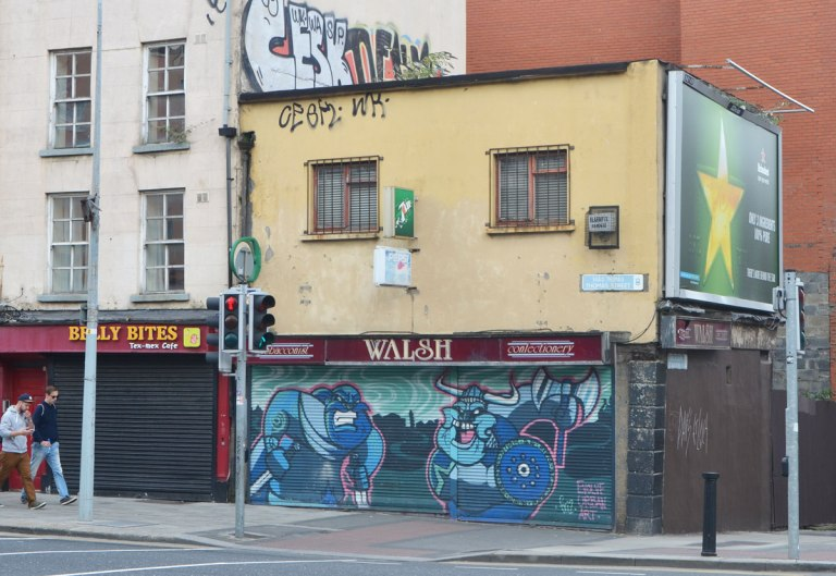 a street corner in Dublin, two men are walking on the sidewalk past a shop, Welsh's confectioner that is closed. A street art painting is on the metal screen or awning that covers the window of the shop.