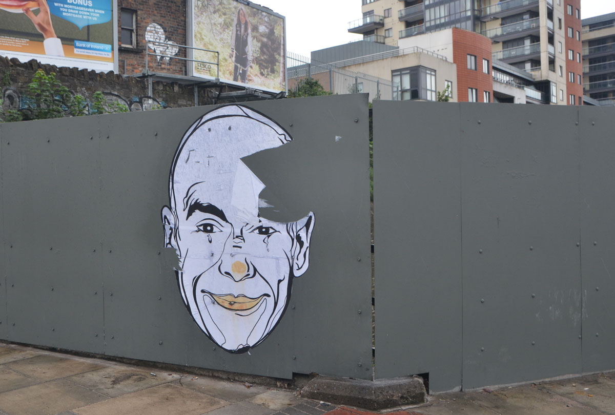 large paste up a man's face, white with black line drawn features, on grey wood hoardings in front of a construction site.