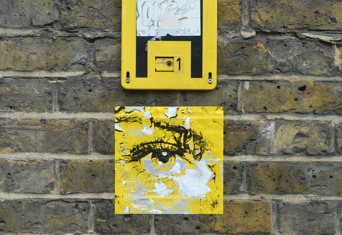 a small square paste up in yellow with black drawing of an eye