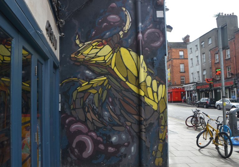 mural of a yellow horned animal on the side of a store, beside the sidewalk