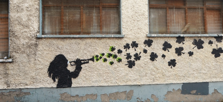 black stencil on a wall, a girl is playing a trumpet and out of the trumpet come shamrocks, three leaf clovers