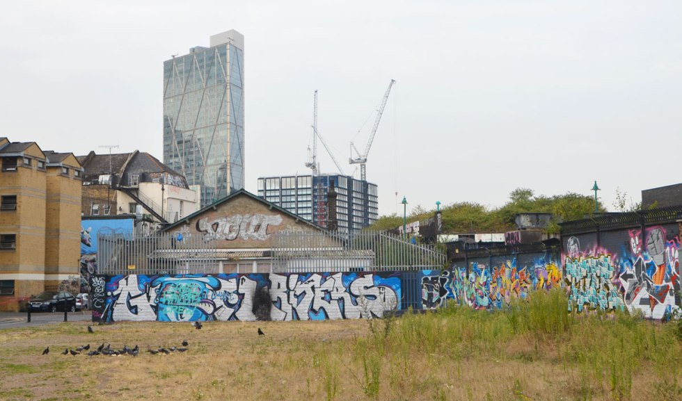 looking across a park, grass in the foreground. A fence covered with graffiti separates the park from buildings, a new glass skyscraper in the distance along with some construction cranes and other new construction.