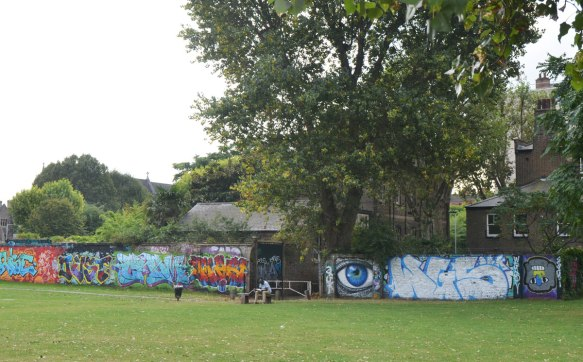 looking across a park, grass in the foreground. A man is sitting on a bench in front of fence covered with graffiti and street art, including a painting of a big blue eye