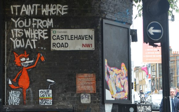 LOndon street sign, Castlehaven Road, Camden, NW1, with an orange cat street art piece beside it. The cat is spraying white words on the black wall, It ain't where you're from but where you are.
