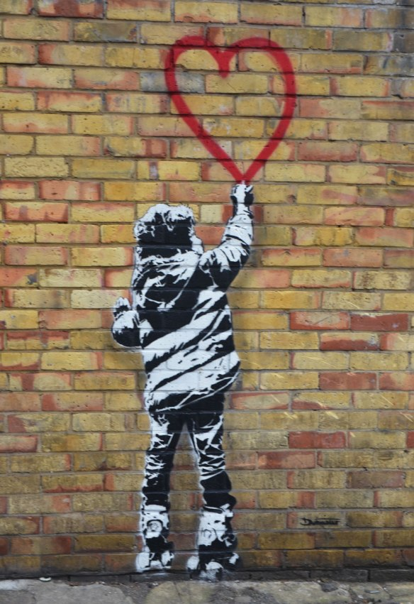 child in winter jacket, drawn in black and white on a brick wall, reaching up and touching the bottom point of a red heart.