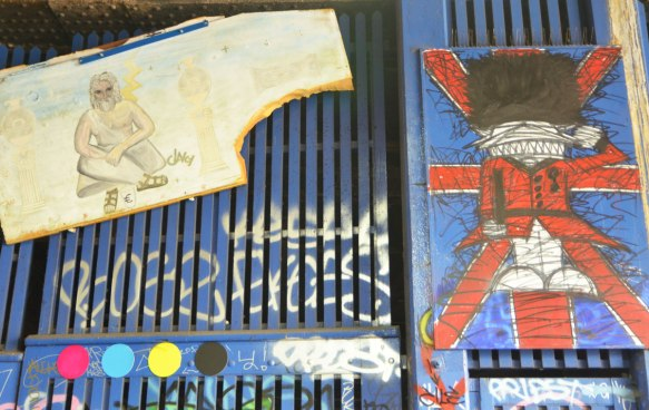 street art and graffiti in Shoreditch England, on Braithwaite Street, a painting of a Buckingham palace guard with its bushy black hat and red uniform, on a union jack by Nathan Bowen and a drawing of a man sitting on a sidewalk by Clancy
