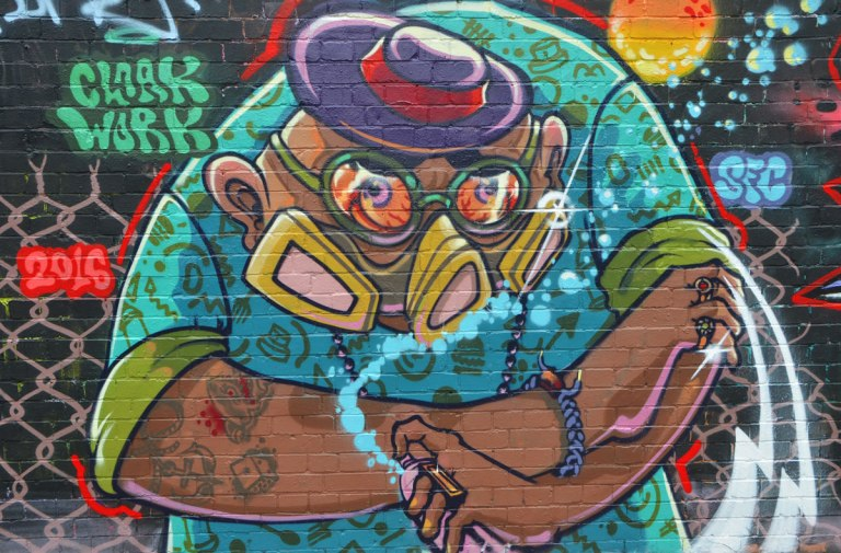 street art and graffiti in Shoreditch England, on Braithwaite Street, mural of a large fat man with gas mask on and spray paint can in hand by cloak work