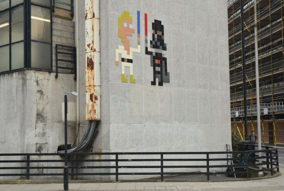 two large invader street artist pieces make of square tiles, a Luke Skywalker in white with a blue light saber and Darth Vader in black with his red light saber, on a grey concrete wall