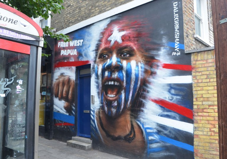 free west papua mural of a young aboriginal boy with a white star on red forehead and rest of face in blue and white stripes, by Dale Grimshaw, about 9 or 10 feet high, blue door in the wall in the mural