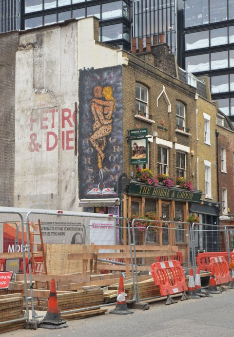 road construction, some older brick buildings and new skyrises in the background. On the wall of the Horse and Groom is a large vertical mural of a naked couple embracing while standing up