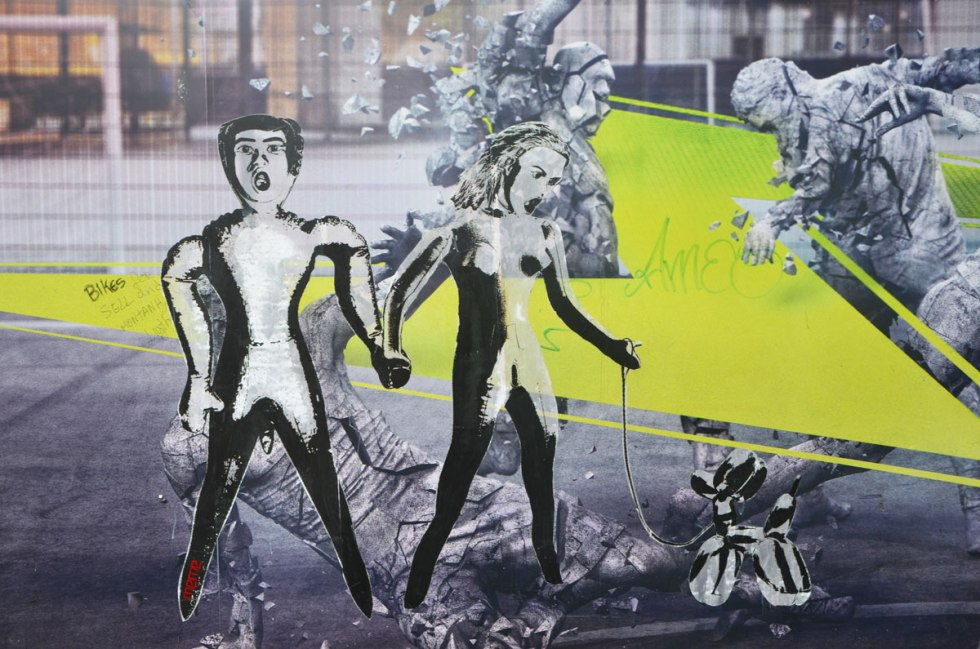 street art paste up of two people, man and woman, that look like inflatabel dolls. The woman is holding the leash of a balloon dog.
