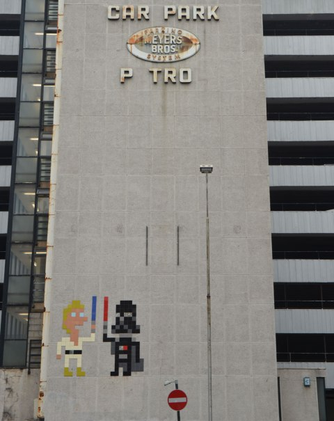 two large invader street artist pieces make of square tiles, a Luke Skywalker in white with a blue light saber and Darth Vader in black with his red light saber, on a grey concrete wall of the Meyers Parking building