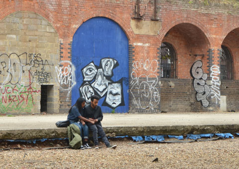 an arch under a brick bridge is covered with plywood and painted blue. On it is a jumbled face in five pieces. Two people are sitting on the kerb in front of it.