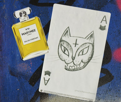 street art and graffiti in Shoreditch England, on Braithwaite Street, a yellow chanel perfume bottle with MaryMee on the label as well as eau de street art. Also a playing card, ace, with cat face on it, and the words @hellothemushroom