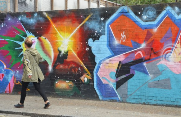 street art and graffiti in Shoreditch England, on Braithwaite Street, a woman walks past construction hoardings covered with street art