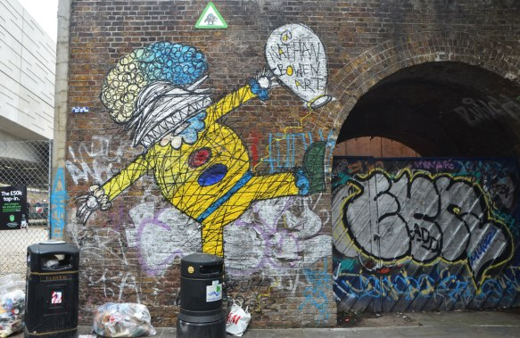 street art and graffiti in Shoreditch England, on Braithwaite Street, a painting by Nathan Bowed on a man in yellow clothes (a clown?)