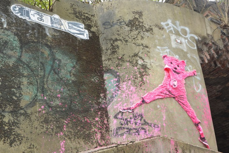 street art and graffiti in Shoreditch England, on Braithwaite Street, a pink teddy bear with terry cloth body high on a wall, beside a black and white pasteup of a bomb