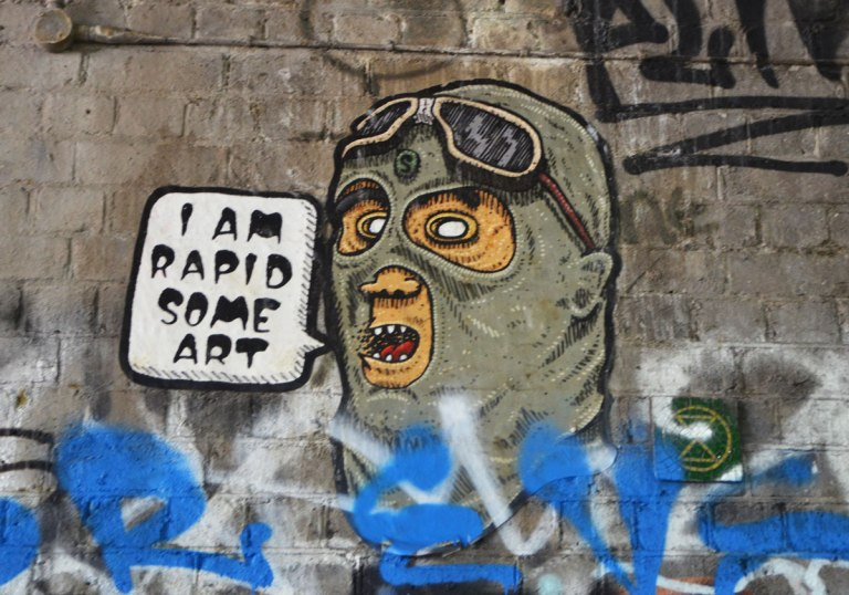 street art and graffiti in Shoreditch England, on Braithwaite Street, a painting of a man's head wearing balaclava and goggles, with word bubble that says I am Rapid Some Art