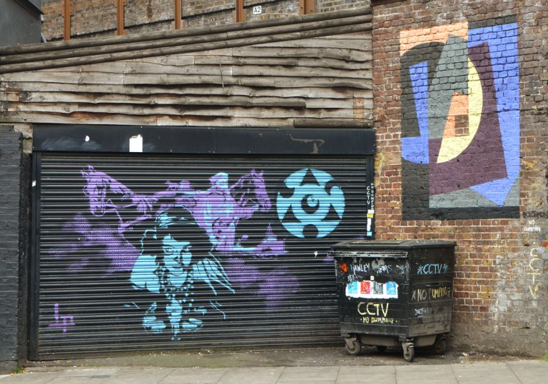 painting on a black metal garage door of a blue woman and a purple horse