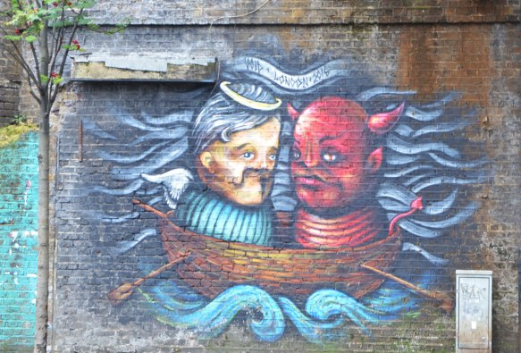 street art painting on a man in a tub floating in the water beside a figure that is the red devil beside him.