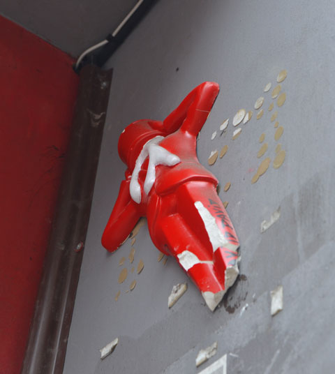a 3 D figure in red attached high up on a wall