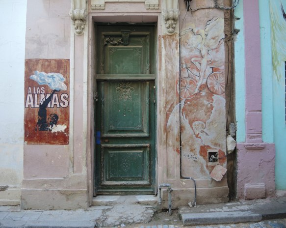 an old green wood door on a building. on one side is a red poster with a black silhouette of the upper part of a man with one arm reaching to the clouds as well as the words a las almas, on the other side of the door is a painting in pinks and bieges of a winged woman on bike riding on top of the globe