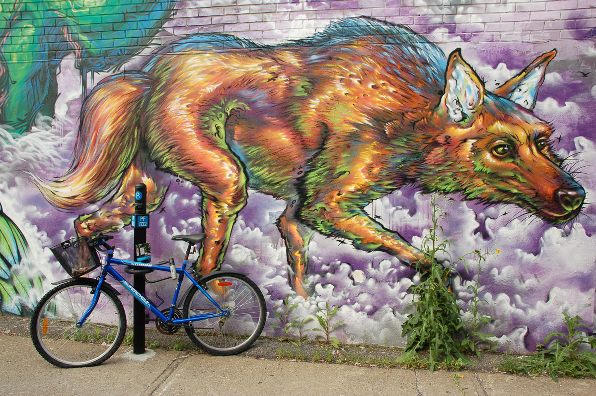 street art, graffiti, animals painted on a wall - an ugly awkward looking dog paces in a mural. The dog looks like it's walking on the sidewalk. A bike is parked in front of it