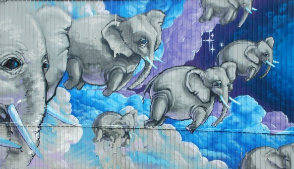 street art, graffiti, animals painted on a wall - elephants flying over blue and purple clouds and sky