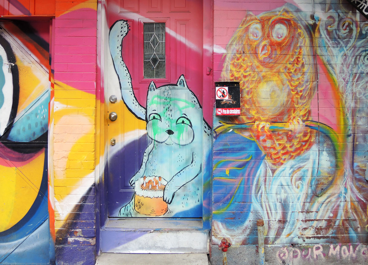 street art, graffiti, animals painted on a wall - a blue dog (or cat?) in a doorway, also an owl has been painted on the wall beside that door