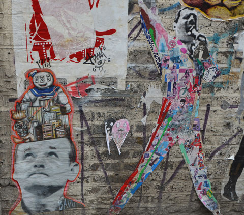 graffiti and street art on fashion street in shoreditch east london, paper paste ups of actor Bill Murray's head looking upwards with the marshmallow guy from the movie Ghostbusters above it, a paper paste up of Freddie Mercury singing with his body made of a collage of other pictures and peoplr