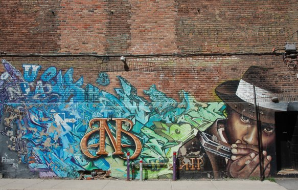 a large brick wall in Montreal with the bottom part covered with a mural. on the right is an image of a black man in a black hat playing the harmonica. The rest is text and tag like shapes in blues and greens. RIP.