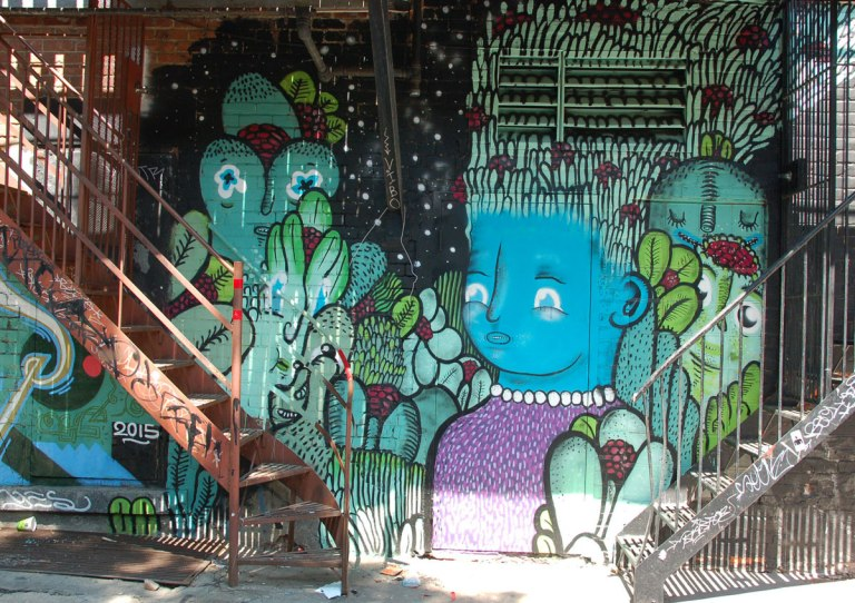 under a balcony with two sets of stairs in front of it, a mural with a blue faced girl as well as some other creatures