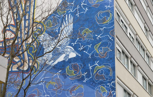 part of a larger mural, a white bird in flight, with a long nexk, surrounded by blue sky with a lot of flowers in the sky . The flowers are line drawings in yellows and white