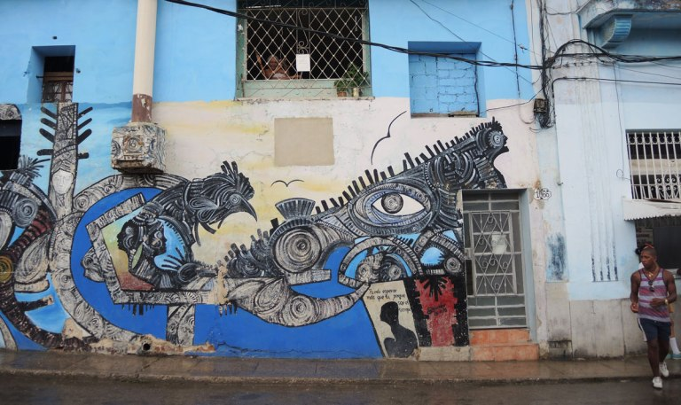 colouful mural on a blue building in havana cuba - a woman looks out from a window above the mural