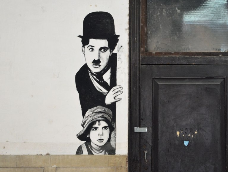 black and white street art piece of Charlie Chaplin looking around the edge of a door - the door is real. A young boy is with Charlie Chaplin