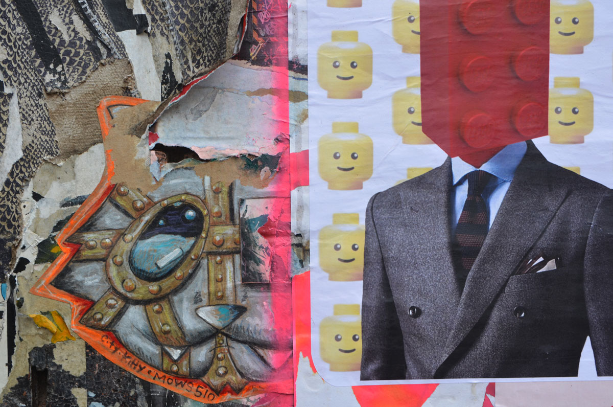 graffiti and street art on fashion street in shoreditch east london, paper paste up from face the strange of a man in suit and tie with a red lego brick as a head. little yellow lego heads in a pattern in the background. Also part of a cat head elaborately drawn and colored with the words city kitty mows 510