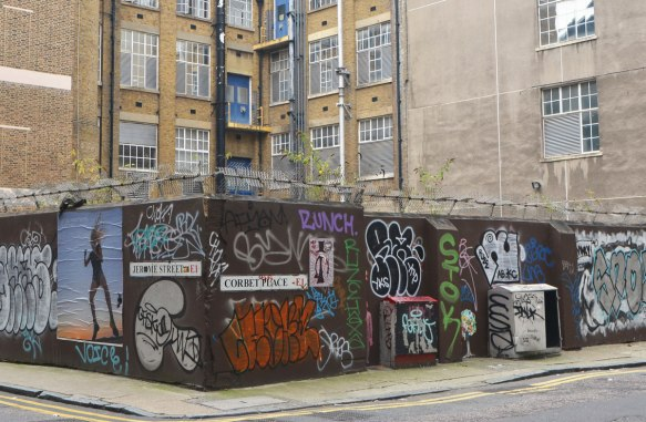 a wall covered with tags and other graffiti, stencils, paint, paste ups, surrounding a yard by an apartment complex, brick building in the background